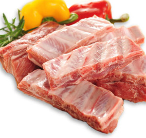 Raw pork ribs on a cutting board and vegetables